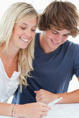 A smiling couple looking at the result of a pregnancy test — Stock Photo