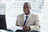 Smiling entrepreneur signing a document — Stock Photo