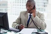 Entrepreneur making a phone call while looking at his computer — Stock Photo
