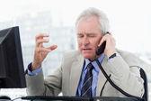 Irritated senior manager on the phone — Stock Photo
