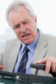 Portrait of an angry senior manager hanging up — Stock Photo