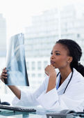 Portrait of a female doctor looking at a set of X-rays — Stock Photo