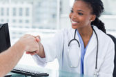 Smiling female doctor shaking a hand — ストック写真