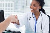 Usmívající se žena doktor třes rukou — Stock fotografie