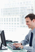 Side view of a smiling office worker using a monitor — Stock Photo