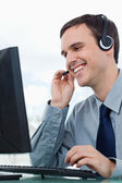 Portrait of a smiling office worker using a headset — Stock Photo