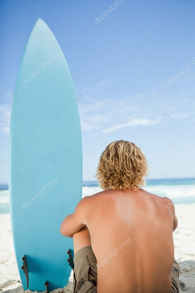 Blonde man sitting down with his arms around his legs next to his surfboard — Stock Photo #10330503