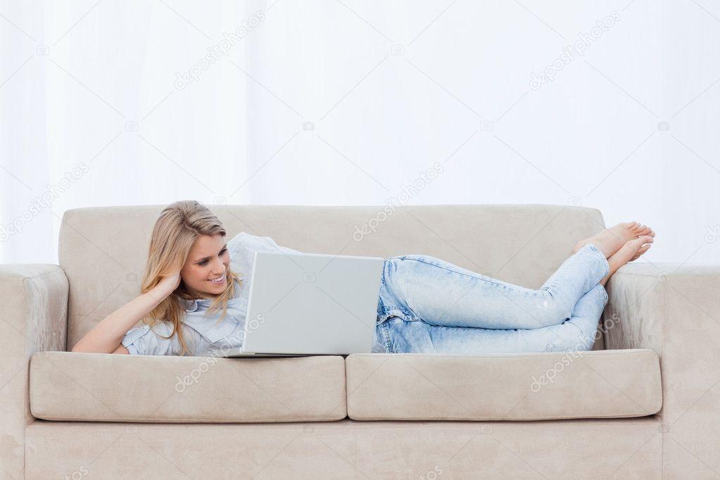 une femme allong e sur un canap pos sa t te sur sa main est avec h photographie. Black Bedroom Furniture Sets. Home Design Ideas