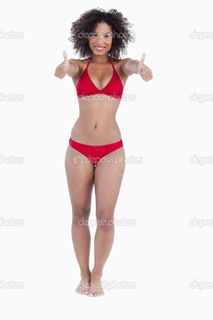 Smiling woman in beachwear placing her thumbs up against a white background  Stock Photo #10334074