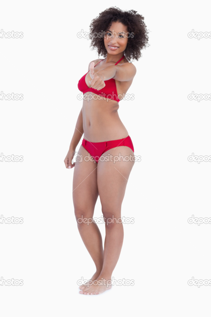 Smiling woman in swimsuit placing her thumbs up against a white background — Stock Photo #10334078