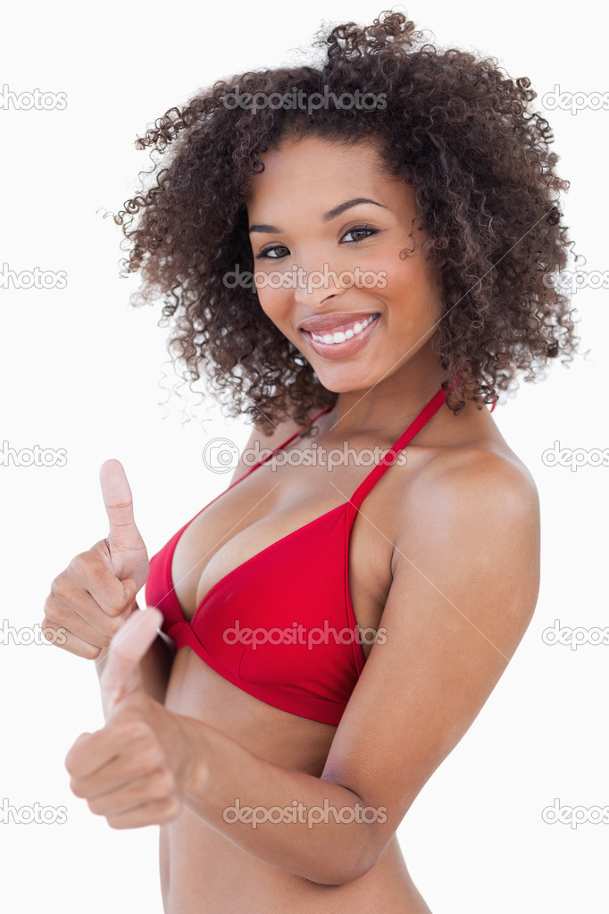 Attractive brunette woman looking at the camera while putting her thumbs up  Stock Photo #10334157