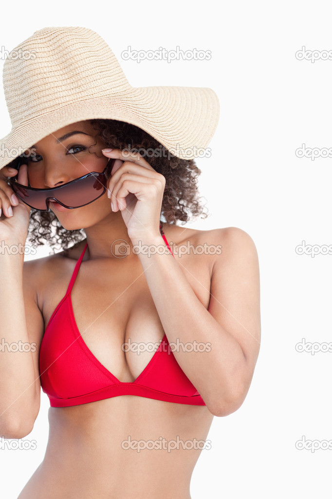 Young woman in beachwear putting on her sunglasses against a white background — Stock Photo #10334192