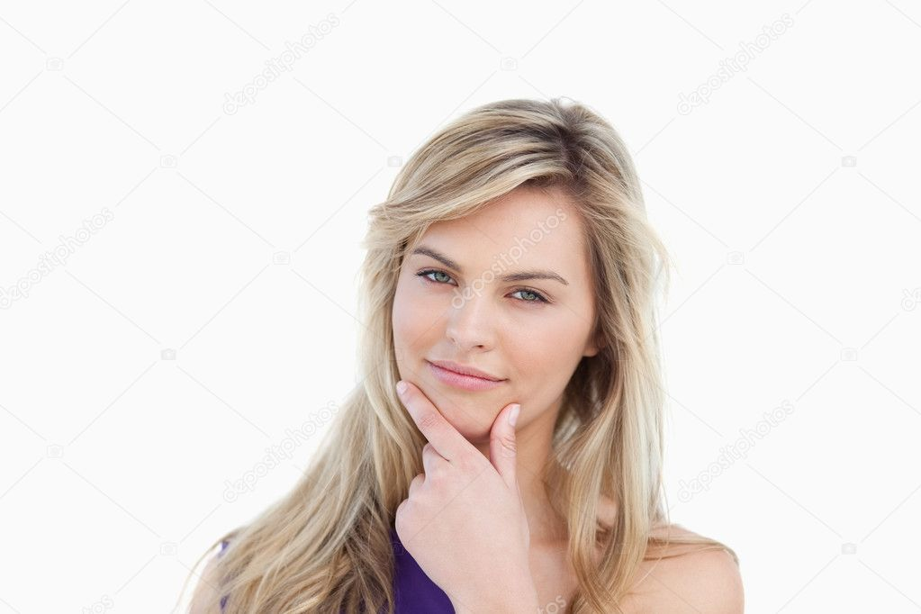 Thoughtful young woman placing her fingers on her chin against a white background  Stock Photo #10334225