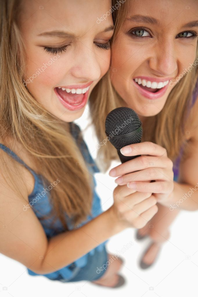 High-angle shot of two happy young blonde singing against white background — Stock Photo #10335403