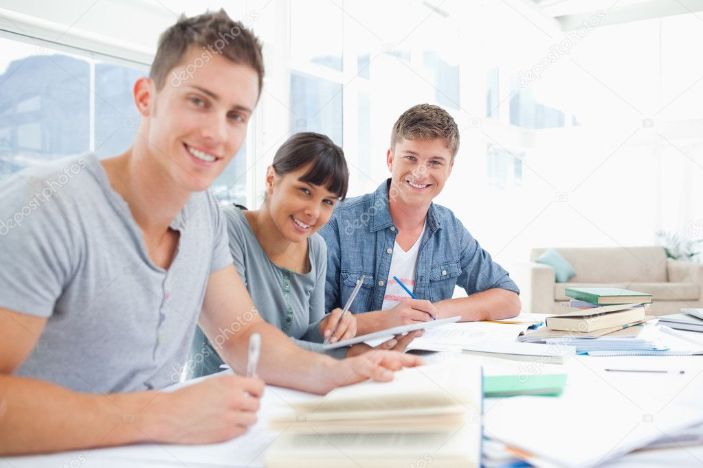 A group of smiling students look into the camera as they all do homework — Stock Photo #10336526