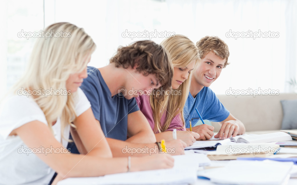 A man smiling while he looks into the camera as he sits with his friends studying  Stock Photo #10337128
