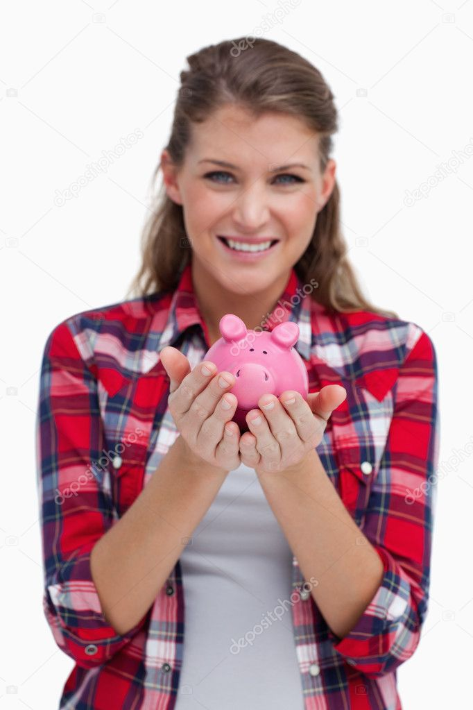 Portrait of a woman holding a piggy bank against a white background — Stock Photo #10338426