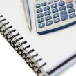 Angled notebook with pencil and pocket calculator — Stock Photo #10578910