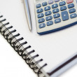 Angled notebook with pencil and pocket calculator - Stock Photo