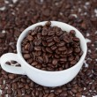 Small white cup of coffee with coffee beans - Photo