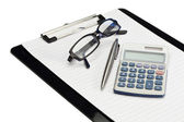 Angled note pad, pen, glasses and pocket calculator — Stock Photo