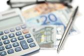 Money, pen, glasses and angled pocket calculator — Stock Photo