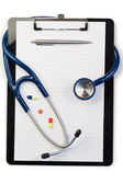 Note pad and stethoscope with pen at the top and pills — Stock Photo