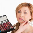 Pretty woman having her make up done by a make up artist — Stock Photo