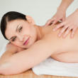 Attractive brunette getting a massage while lying down — Stock Photo
