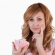 Blond-haired woman thoughtful while holding her broken piggybank — Stock Photo