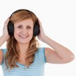 Attractive blond-haired woman listening to music — Stock Photo #10586075