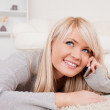 Beautiful happy blond woman talking on cell phone lying down on — Stock Photo #10586448