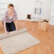 Attractive woman rolling up a carpet to prepare to move house — Stock Photo