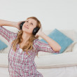 Cute blond-haired woman listening to music with headphones — Stock Photo #10587759