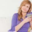 Pretty red-haired woman holding a cup of coffee while sitting on — Stock Photo #10587800