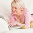 Young attractive woman relaxing with a laptop while lying on a s — Stock Photo