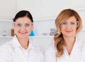 Two female scientists with safety glasses looking at the camera — Stock Photo