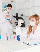 Dark-haired and blond-haired scientists conducting an experiment — Stock Photo