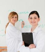 Joven científico escribiendo una fórmula ayudada por su asistente femenino — Foto de Stock