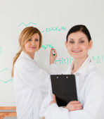 Young scientist writting a formula helped by her female assistan — Stock Photo