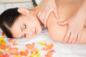 Cute brunette lying down and getting a massage — Stock Photo