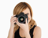 Blond-haired woman taking a photo with a camera — Stock Photo