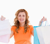 Attractive blond-haired woman showing her shopping — Stock Photo