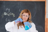 Young blond-haired woman carrying out an experiment — Stock Photo
