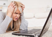Attractive blond woman frustrated with her computer lying on a c — Stock Photo