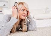 Linda mulher loira com fones de ouvido deitado em um tapete — Fotografia Stock