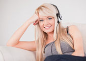Attractive young blond woman with headphones sitting in a sofa — Stock Photo