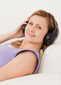 Attractive blond-haired woman listening to music lying on the so — Stock Photo