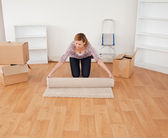 Blond-haired woman rolling up a carpet to prepare to move house — Stock Photo