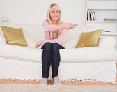 Good looking blonde female watching tv while sitting on a sofa — Stock Photo